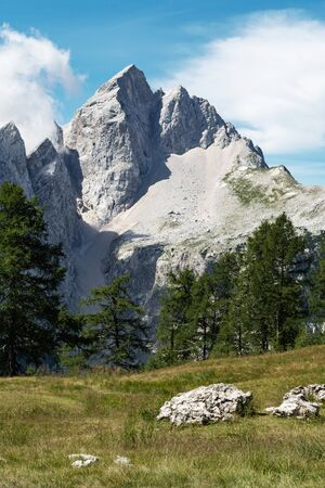 Beautiful scene of high mountain peak with a vast scree and green pasture in Julian Alps in Slovenia. Alpinism, mountain climbing, nature, danger, geology and weather concepts