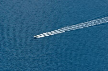Aerial view of speeding motor boat on a deep blue colored sea. Luxury, vacation, trafficking and war on drugs concepts