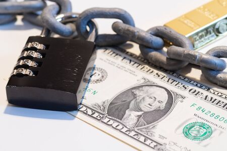 Closeup of one US Dollar banknote lying under metallic chain with black combination padlock and gold bar in background. Gold standard, fiat money, financial safety and fiscal policy concepts