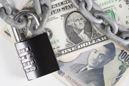 Closeup of US Dollar and Japanese Yen banknotes under metallic chain and black combination padlock. Financial safety, currencies, money protection, fiat money and fiscal policy concepts