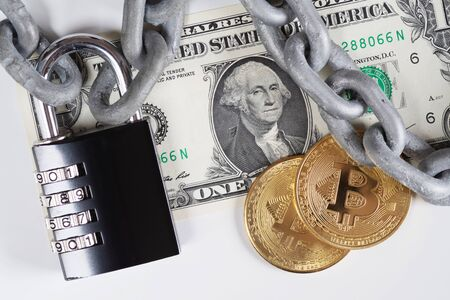 Closeup of one US Dollar banknote and two golden Bitcoin coins lying under metallic chain with black combination padlock. Cryptocurrency, digital money, financial safety and fiscal policy concepts