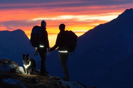 Backpacking hiker couple with border collie dog holding hands and watching magical sunset sky. Hiking, emotions, pets, optimism and relationship concepts