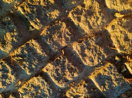 Stone paved ground with granite cobblestone lit by sunlight during golden hour. Architecture, history and urbanism concepts. 스톡 콘텐츠