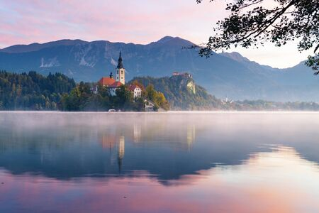 Beautiful view of lake Bled during sunrise in autumn. Fog lingering over the lake with island and old catholic church. An old castle with mountains visible in background. Religion, travel and tourism.