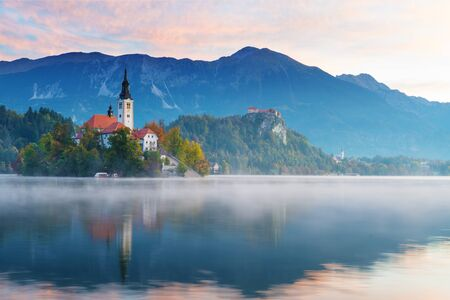 Beautiful morning view of lake Bled during sunrise in autumn. Old catholic church on island and old castle with mountains visible in background. Religion, travel and tourism. 版權商用圖片