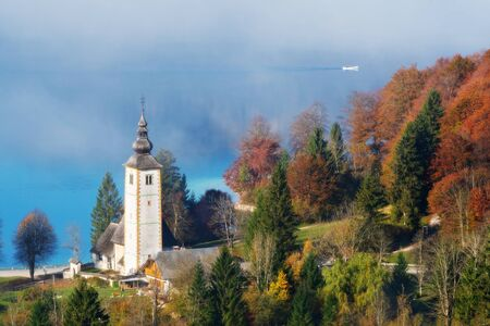 Magnificent view of catholic church of John the Baptist at lake Bohinj in autumn and canoe emerging from fog on a sunny morning in Slovenia. Travel, tourism and beauty of nature concepts 版權商用圖片