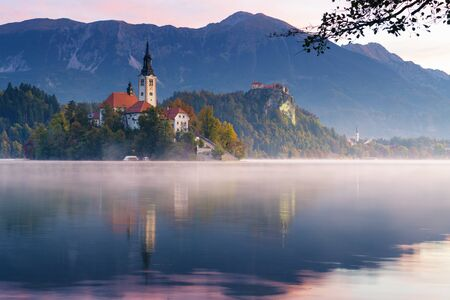 Idyllic view of lake Bled during sunrise in the autumn. Mist lingering over the lake with catholic church on island and old castle with mountains in background. Religion, travel and tourism. 版權商用圖片