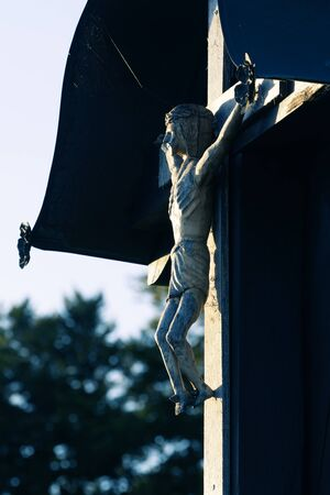 Wood carved representation of crucifixion of Jesus Christ, a catholic religious sign, lit by setting sun in rural area. Religion, catholicism, christian faith and signs concepts. 版權商用圖片
