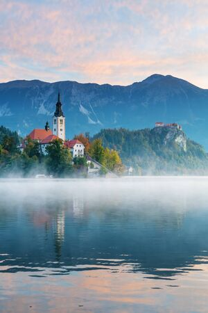 Beautiful morning view of lake Bled with beautiful sky during sunrise in autumn. Old catholic church on island and old castle with mountains visible in background. Religion, travel and tourism.
