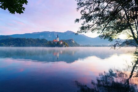 Panoramic view from the shore of lake Bled during sunrise in autumn. Old catholic church on island and old castle with mountains visible in background. Religion, travel and tourism.