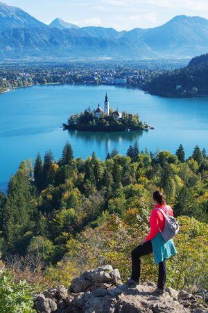 Young woman hiker with backpack enjoying the view of alpine lake Bled and mountains in background. Slovenia, Europe. Landmarks, travel, tourism and beauty of nature concepts.