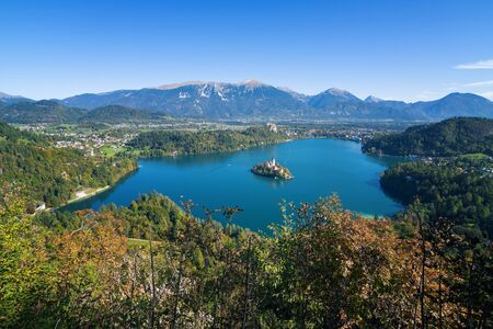 Panoramic view of lake Bled with island in the middle and old castle and Alps in background in Slovenia on a sunny autumn day. Landmarks, travel, tourism and beauty of nature concepts