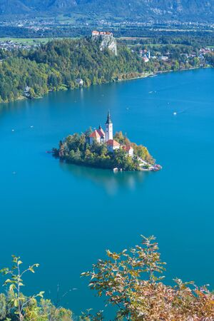 Aerial view of lake Bled with island in the middle and old castle in background in Alpine region in Slovenia on a sunny autumn day. Landmarks, travel, tourism and beauty of nature concepts