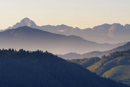 Mount Triglav, highest peak of Julian Alps, in background, with coniferous forests and foggy valleys in foreground during sunset in autumn. Alps, mountaineering, travel and beautiful nature concepts.
