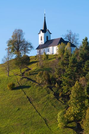 St. Jacob church on top of the hill at the beginning of golden hour in Slovenia. Religion, hiking, travel and nature concepts. 版權商用圖片