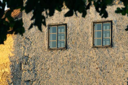 Two windows on an old building with cracked facade lit from side by setting sun