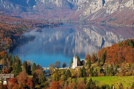 Magnificent view of lake Bohinj and the church of John the Baptist in the colors of autumn on a sunny morning in Slovenia. Travel, tourism and beauty of nature concepts