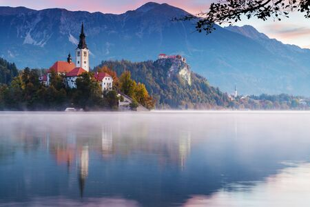 Beautiful morning at lake Bled during sunrise. Mist lingering over the lake with catholic church on island and old castle with mountains in background in early autumn. Religion, travel and tourism.