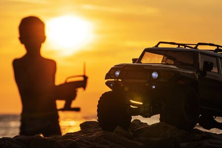 Closeup of a remote controlled toy car and a silhouette of a boy holding a radio controller on the beach during sunset. Play, youth, childhood, hobby and vacation concepts