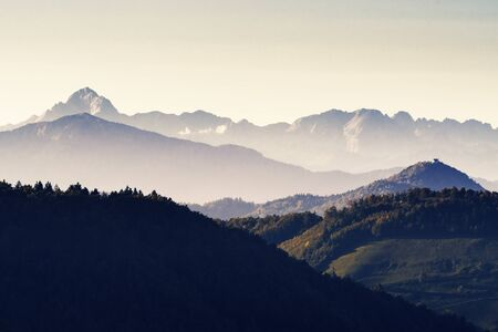 Beautiful mountainous landscape with coniferous forests and foggy valleys and mount Triglav, the highest peak of Julian Alps, in background during sunset in autumn. Forestry and travel concepts.
