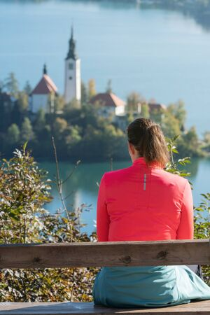 Young woman hiker enjoying the view of church on island on lake Bled below. Slovenia, Europe. Religion, faith, self-reflection, travel and tourism concepts.