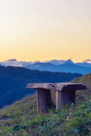 Old vacant wooden bench on the hilltop with nice scenic view of Julian Alps in the evening in Slovenia. Travel, hiking, atmosphere, magical nature and mood concepts.