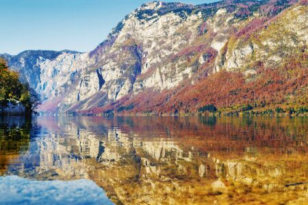 Beautiful autumnal landscape in vibrant colors reflecting in lake with mountains in background