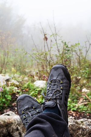 Crossed hikers feet with gray trekking shoes and foggy forest in background. Hiking, backpacking and equipment concepts.