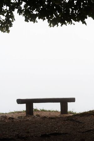 Silhouette of an old wooden bench on hilltop and leaves of overhanging tree isolated on white on a foggy day in Slovenia. Travel, hiking, atmosphere, loneliness and mood concepts. 版權商用圖片