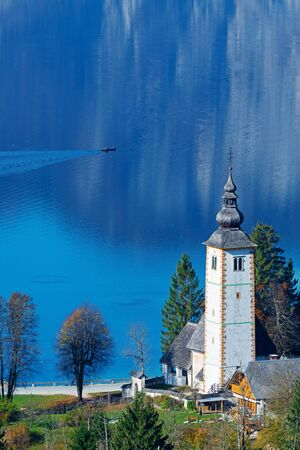 Wonderful view of catholic church of John the Baptist at lake Bohinj in autumn and lone fisherman in canoe on a sunny morning in Slovenia. Travel, tourism and beauty of nature concepts