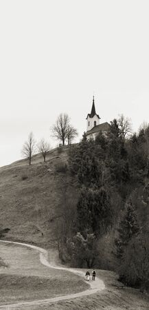 Christian church of St. Jacob on top of the hill and hikers walking towards it on a gravel country trail. Nature, hiking, travel and religion concepts 版權商用圖片