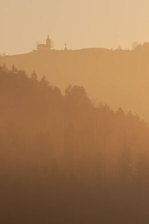 Beautiful view of coniferous slopes and catholic church with cross on top of the hill in evening haze lit by setting sun. Nature and religion concepts 스톡 콘텐츠