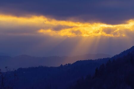Rays of sunlight shining through clouds over dark landscape in the evening. Faith, religion, hope and nature concepts. 版權商用圖片