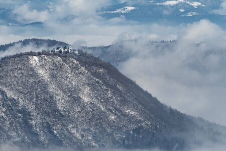Aerial view of an old catholic church on top of the mountain in winter time. Smarna Gora aka Mt. St. Mary in vicinity of Ljubljana, Slovenia.