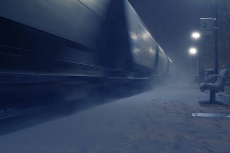 Passing cargo train in blurred motion at train station on a winter night. Transportation and logistic service concepts