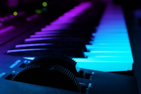 Closeup of synthesizer keyboard with focus on pitch and modulation wheels in dark ambient illuminated by pink and blue light. Music and instruments