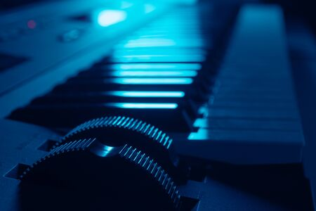 Closeup of electronic synthesizer keyboard with focus on pitch and modulation wheels in dark ambient illuminated by blue light. Music and instruments 版權商用圖片