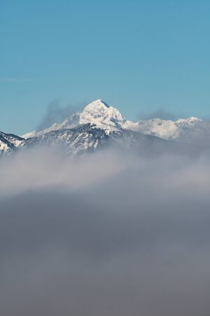Beautiful view of snow capped Mount Triglav, the highest peak in Slovenian Julian Alps, on a clear winter morning with dense fog beneath 版權商用圖片