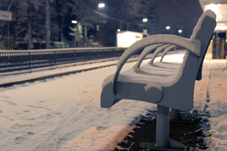 Vacant bench covered with snow at an empty train station at night. Expectation, loneliness and transportation concepts