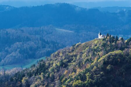 Autumn panorama with old christian church on top of hill in Slovenian countryside. Nature, hiking, travel and religion concepts