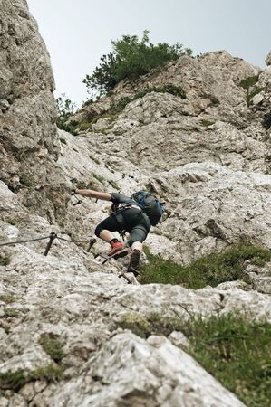 Male mountain climber in steep vertical wall climbing the via ferrata in Julian Alps. Alpinism, mountain climbing and protective gear concepts