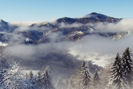 Beautiful wintry scene of snow covered landscape and hills in morning fog. Hiking, seasonal, beauty of nature and environment concepts.