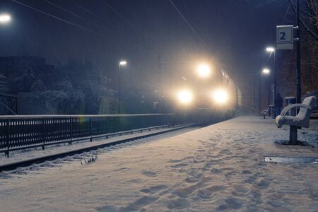 Freight train with strong headlights arriving at station on a snowy night. Travel, transportation and season concepts