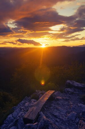 Beautiful sunset and colorful clouds over landscape from top of the hill. Hiking, self-reflection, colors in nature, optimism and weather concepts.
