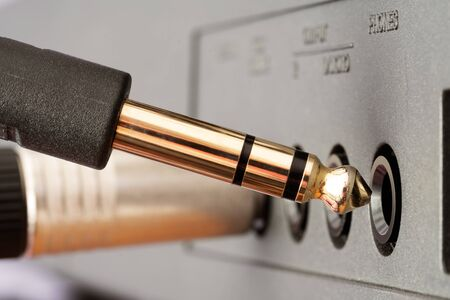 Closeup of golden TRS phone jack audio connector being plugged into socket on audio device. Music, audio, hi-fi, connectivity and sound reproduction.