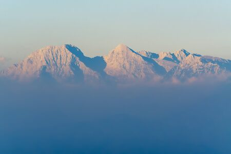 View of sunlit Alps during sunset and fog covered lower regions in Slovenia