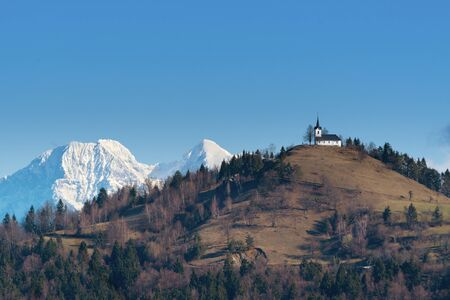 Beautiful landscape with an old catholic church of St. Jacob on top of the hill and snowy alpine peaks in background. Religion, optimism, hiking and tourism concepts