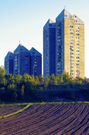 Freshly plowed field and residential buildings in background lit by setting sun. Urbanism, agriculture and sustainability concepts