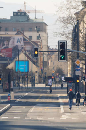 Ljubljana, Slovenia - March 17, 2020: Working traffic lights in downtown Ljubljana, Slovenia on nearly empty streets with few bicycle riders and pedestrians during the Coronavirus Covid-19 outbreak