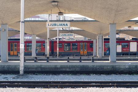 Ljubljana, Slovenia - March 17, 2020: Empty platforn in Ljubljana train station with vacant benches and train during the Coronavirus Covid-19 outbreak, Ljubljana, Slovenia